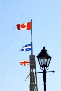 Flags of Canada, Quebec, and Montreal at the waterfront.