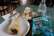 Lunch of a sausage roll, crisps, Victoria sponge.