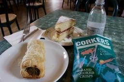 Lunch of a sausage roll, crisps, Victoria sponge.